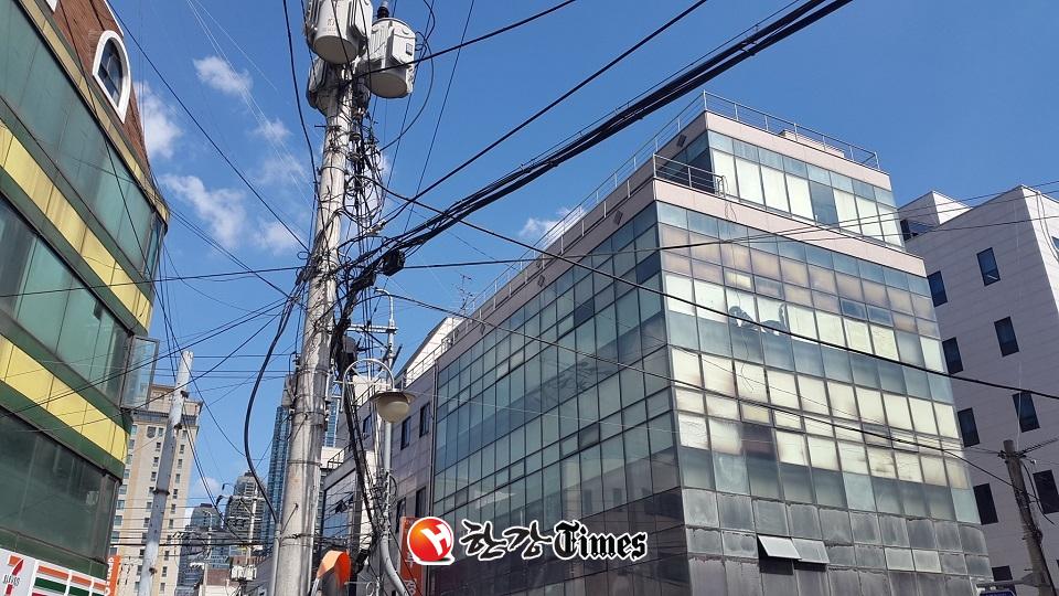 복잡하게 전선들이 얽혀 있는 강남구 논현로 36길 작업전 전신주 모습
